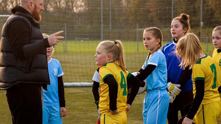 Tränare coachar ett flicklag vid en fotbollsplan