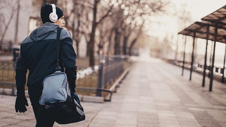 Ung kille går på gångväg på väg till träningen med träningsväska över axeln, och hörlurar över mössan