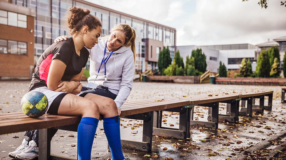 Tränare håller tröstande arm runt en ung idrottstjej som är ledsen