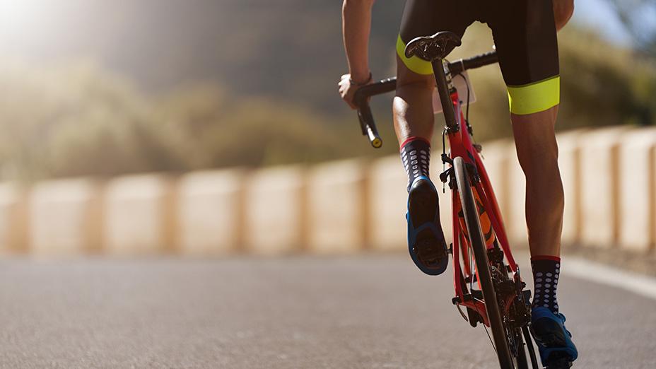 Elitidrottens ansvar rörande ätstörningar. Närbild på en tävlingscyklist som cyklar på en asfalterad väg.